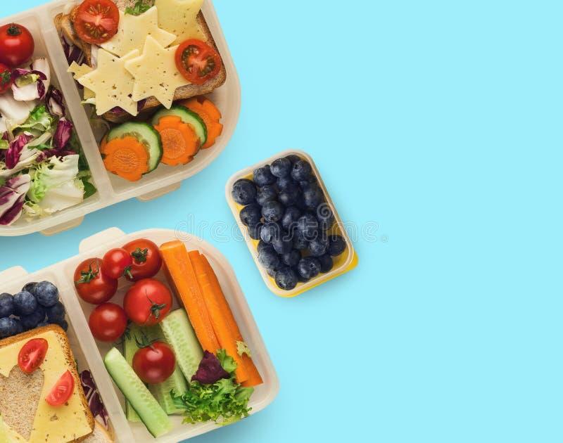 Fiambreras con la comida sana, aislada en azul foto de archivo