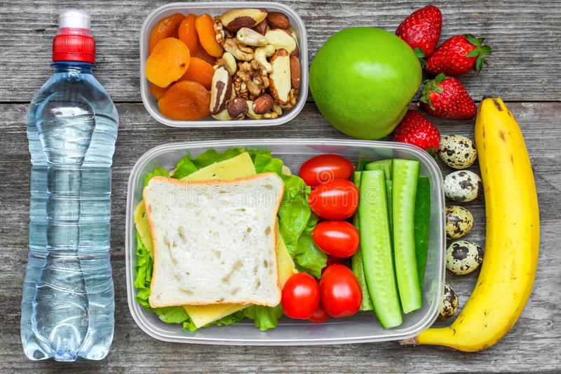 Fiambreras sanas con el bocadillo, huevos y verduras frescas, botella de agua, nueces y frutas imagenes de archivo