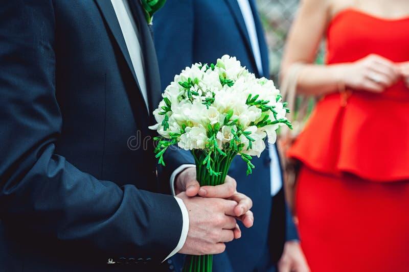 Fiance in een donkerblauw die kostuum houdt een huwelijksboeket van witte bloemen wordt gemaakt stock afbeeldingen