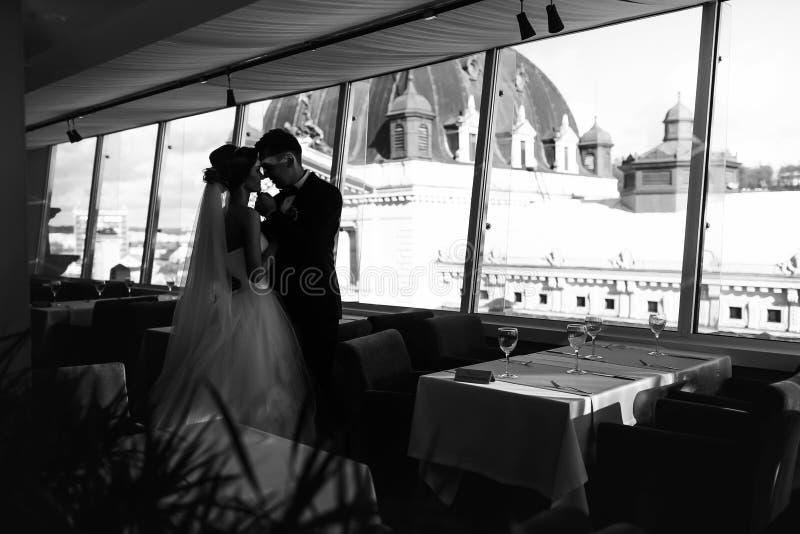 Fiance houdt de kin van de bruid terwijl status vóór panoramische windo royalty-vrije stock foto's