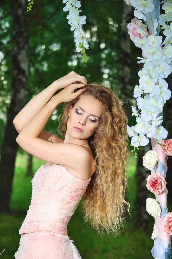 Fiancee in een roze kleding en een boog stock fotografie