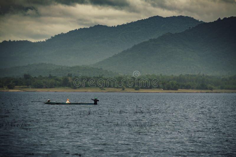 Fianco di una montagna in Tailandia con un peschereccio in un lago fotografia stock libera da diritti