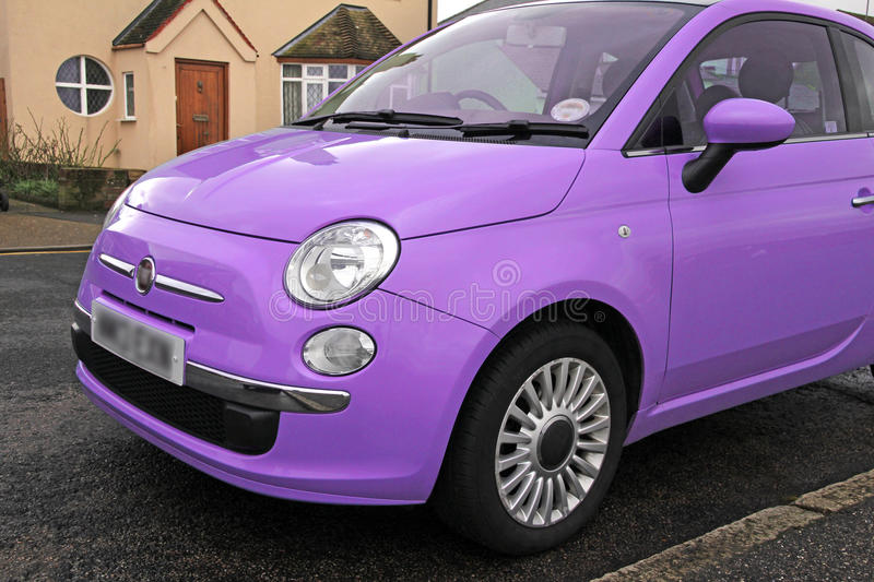 Fiat 500 small modern car. Photo of a modern funky purple sall car parked by kerb stock photo