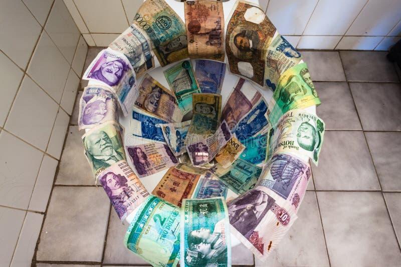 Toalett för valutapengarspolning arkivbilder