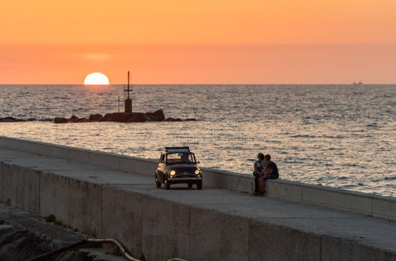Fiat 500 op de achtergrond van het overzees en de zonsondergang stock afbeeldingen