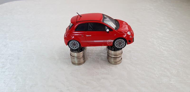 Fiat rosso piccolo 500 supporti del giocattolo su quattro pile di monete israeliane da uno shekel immagini stock libere da diritti
