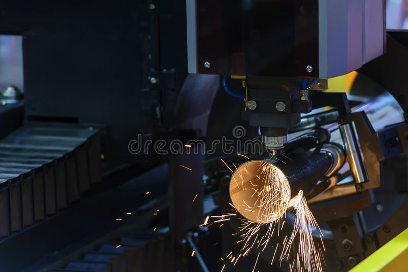 The fiber laser cutting machine cutting the steel pipe. With the sparking light stock image