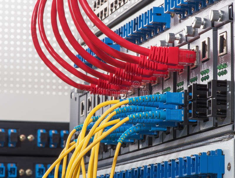 Fiber Optic cables connected to an optic ports stock photography