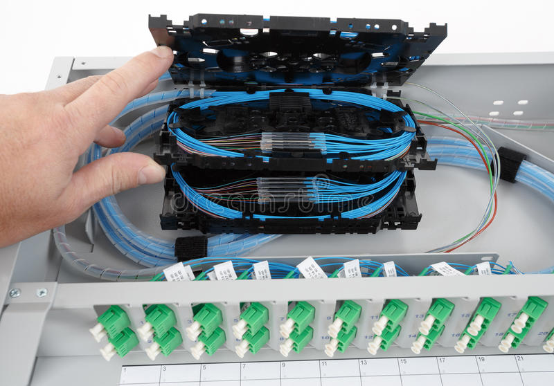 Fiber optic splice cassettes. Stack of fiber optic splice cassettes with protection sleeve and blue fibres installed in optical distribution frame stock photos