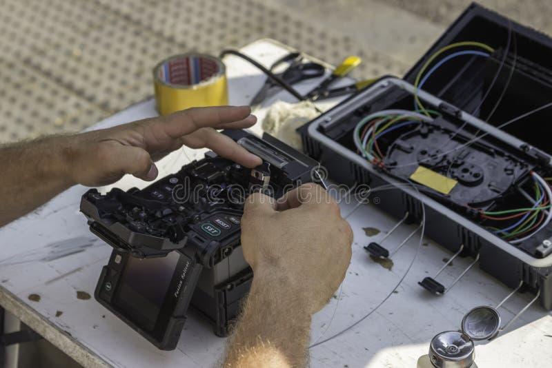 Fiber - optiska teknikerhänder royaltyfri foto