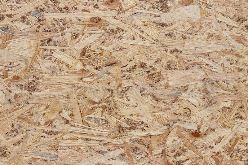 Fiberboard. Compressed light brown wooden plywood texture. Close up surface of pressed wood-shaving plate. Old wooden board bagass stock images