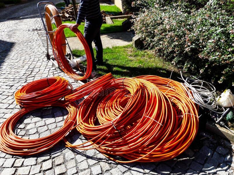 Fibra o cables de fribra óptica anaranjados en el jardín para la excavación imágenes de archivo libres de regalías