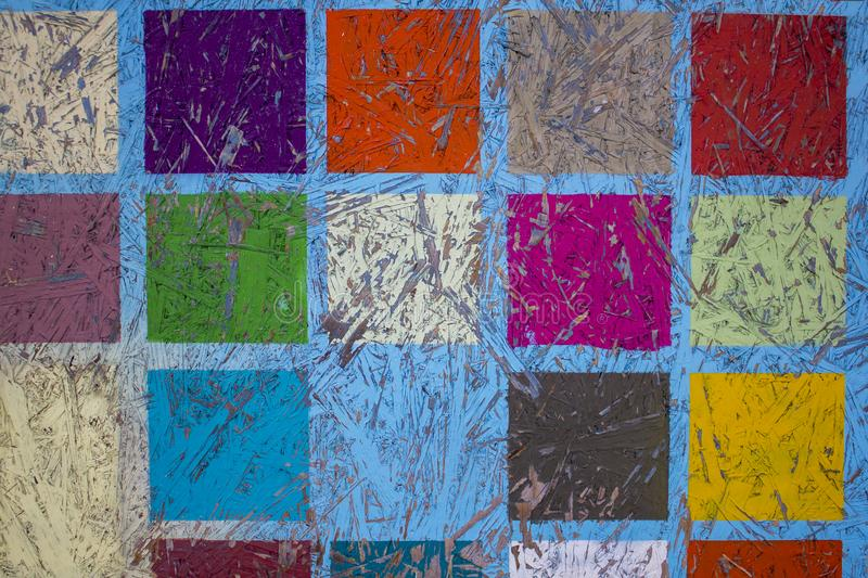 Fibreboard with blue peeling paint and bright multi-colored squares. rough surface texture royalty free stock photography