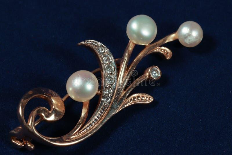 Fibula dell'oro con le perle su fondo blu scuro fotografia stock