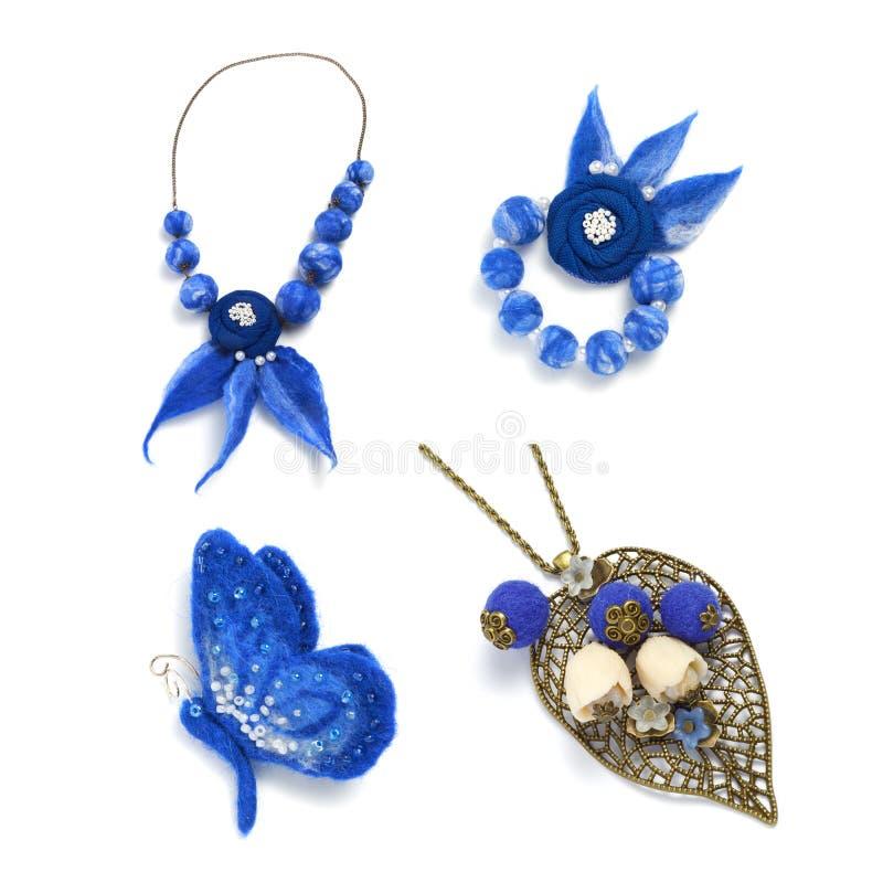Fibula sotto forma di farfalla, di perle e di fatto a mano del braccialetto fatto di feltro su un fondo bianco immagini stock
