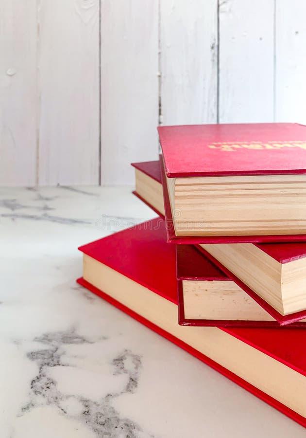 A ficção vermelha, novelas é empilhada nos assoalhos de mármore, fundos de madeira brancos da parede imagem de stock royalty free