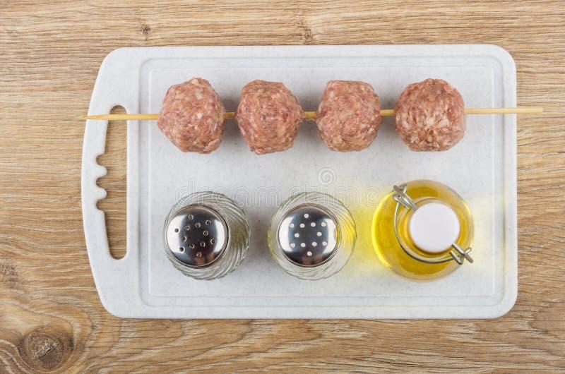 Ficelé sur des boulettes de viande de brochette, sel, poivre, huile sur la planche à découper photos stock