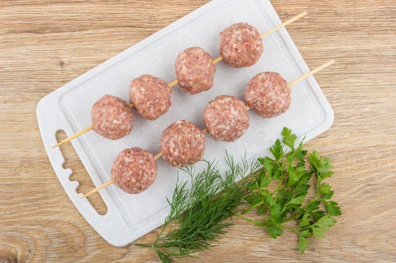 Ficelé sur des boulettes de viande de brochette sur la planche à découper et les verts photographie stock libre de droits