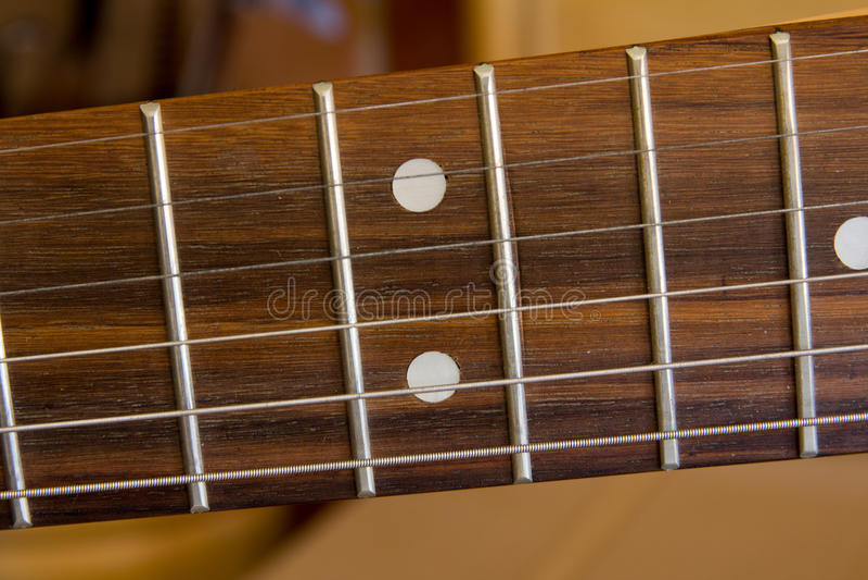 Ficelles de guitare sur un Fretboard images stock