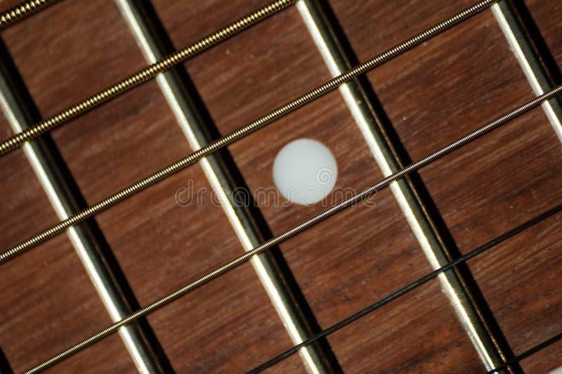Ficelles et fretboard en acier sur la guitare classique photographie stock