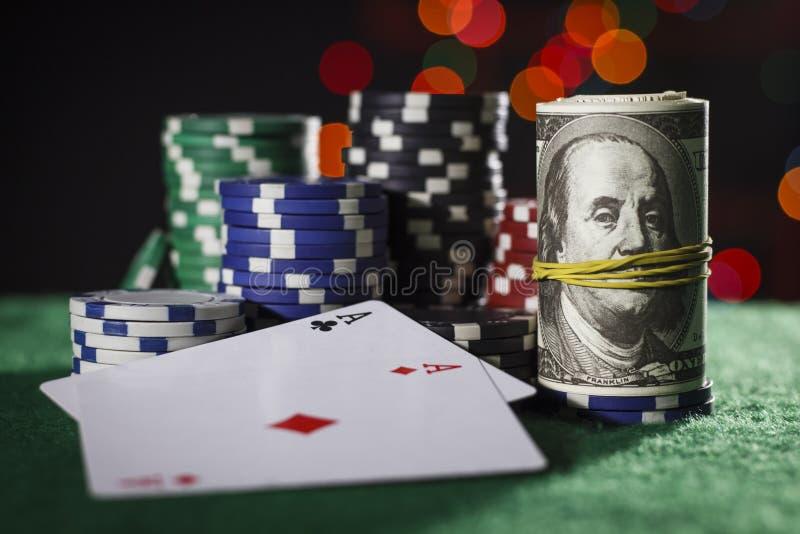 Fichas de póker, dólares y un par de as foto de archivo
