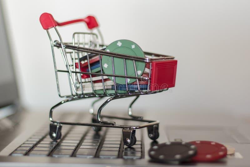 Fichas de póker en un carro de la compra en un ordenador Concepto de juego en línea del apego imágenes de archivo libres de regalías