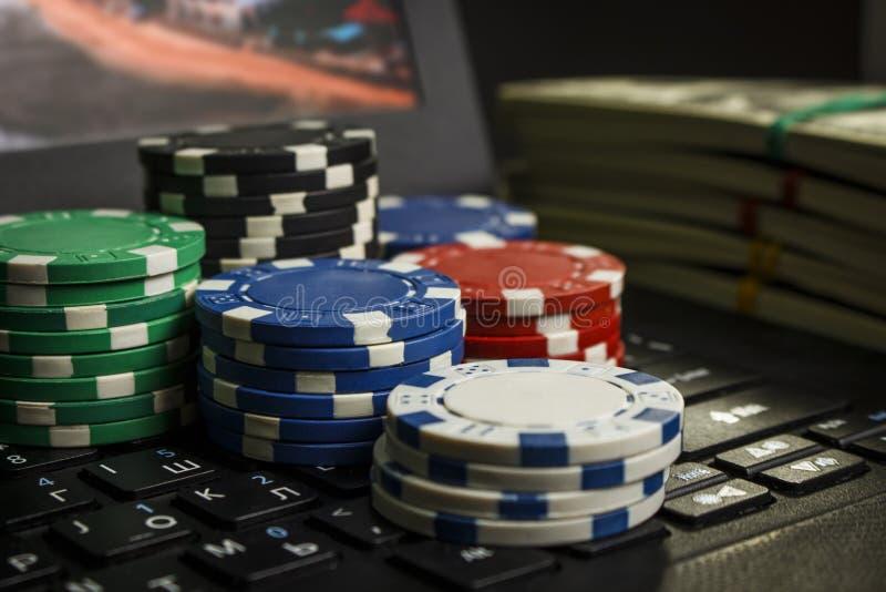 Fichas de póker y paquetes de dólares en un ordenador portátil imagen de archivo libre de regalías