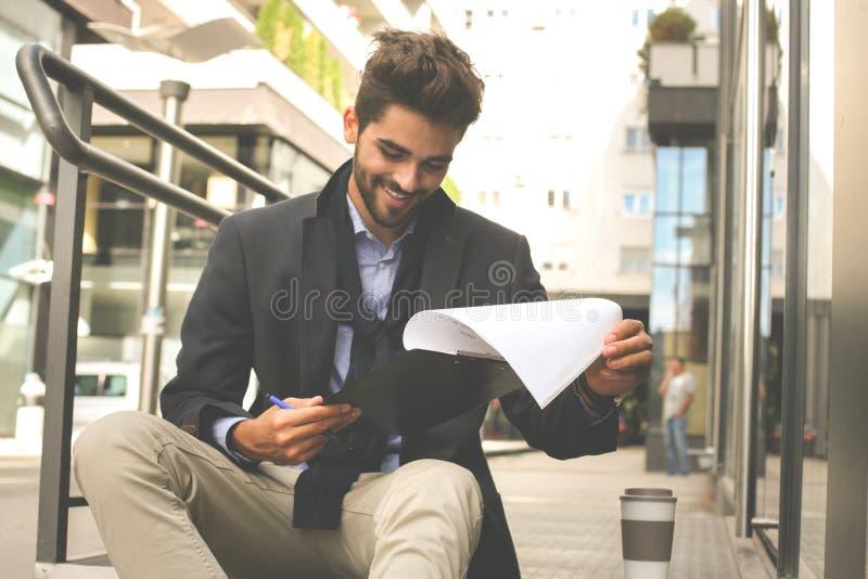 Fichero de tenencia del hombre de negocios y documento de la lectura en la calle fotografía de archivo