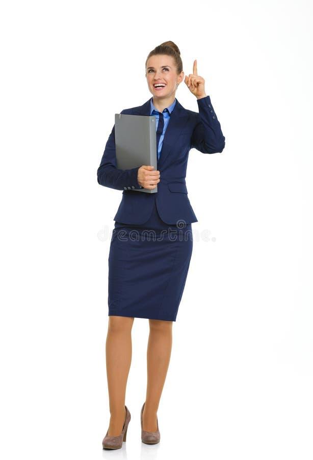 Fichero de tenencia sonriente de la empresaria y el señalar hacia arriba fotos de archivo