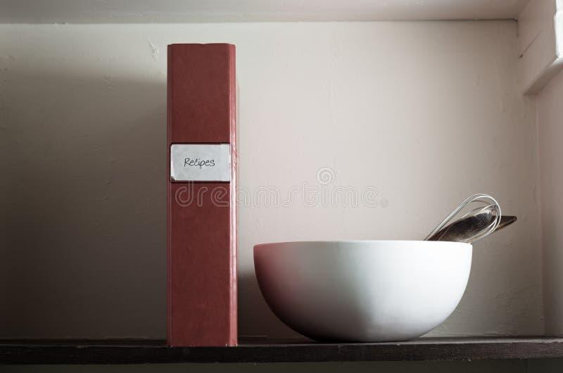 Fichero, tazón de fuente y utensilios de la receta en estante imagenes de archivo