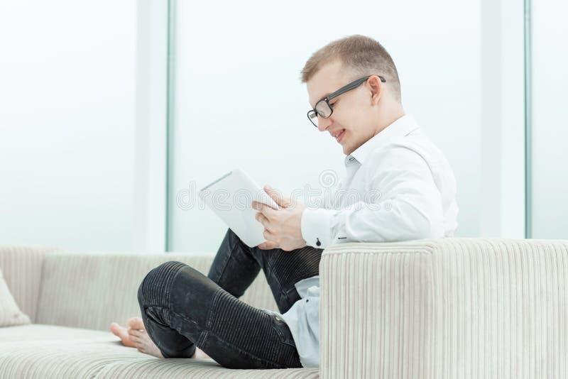 Ficheros de medios de la ojeada del hombre joven en su tableta imagenes de archivo
