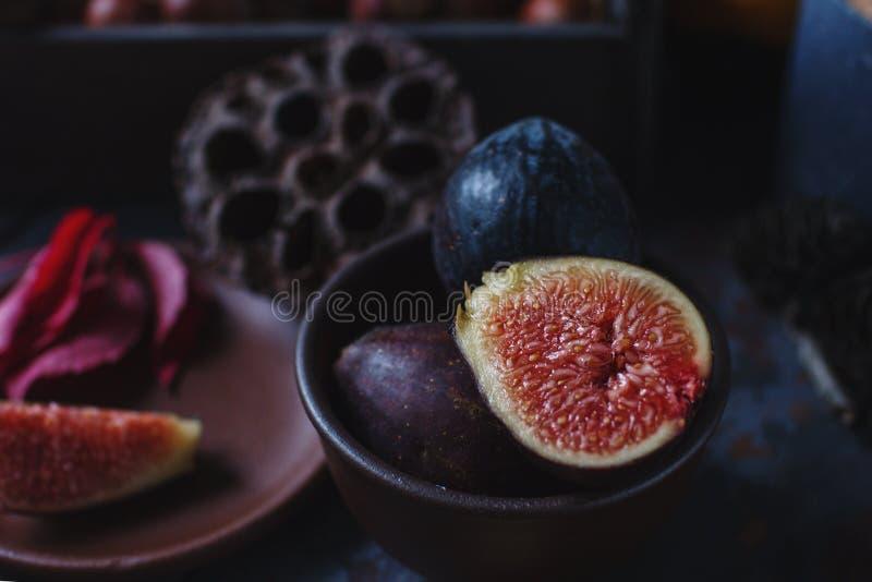 Fichi, dadi e foglie di autunno organici freschi sul bordo di legno e sulla tavola di pietra scura Stile di vita sano, frutta sta fotografie stock