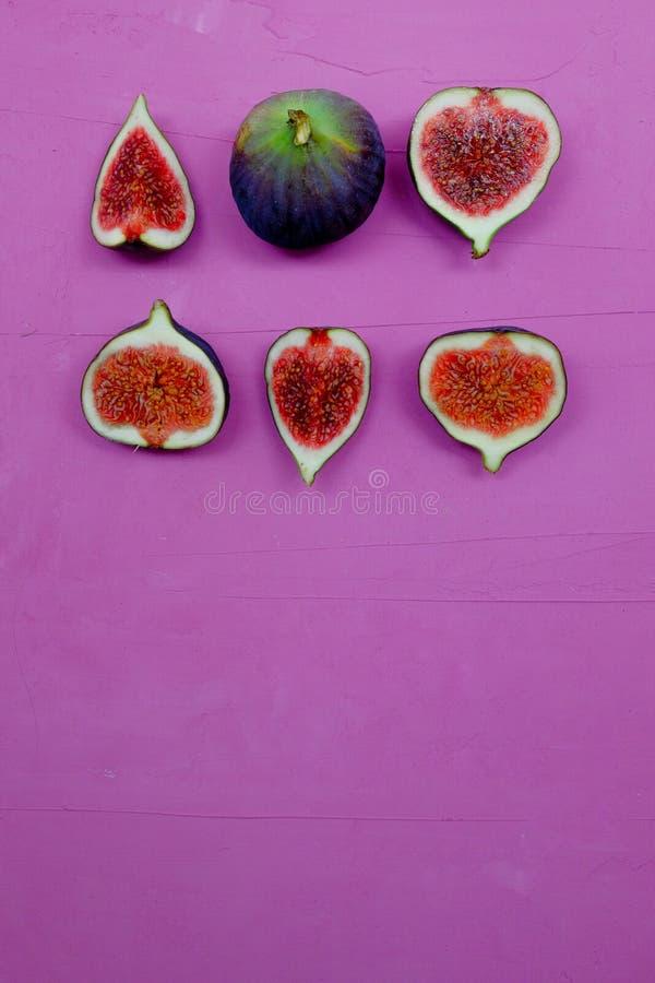 Fichi dolci maturi, frutta con la metà e quarto su fondo porpora immagine stock libera da diritti