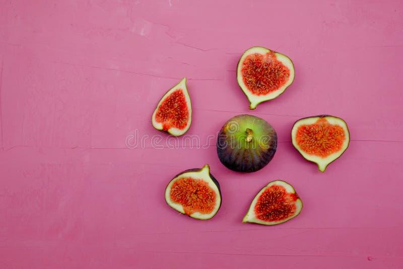 Fichi dolci maturi, frutta con la metà e quarto su fondo rosa immagine stock