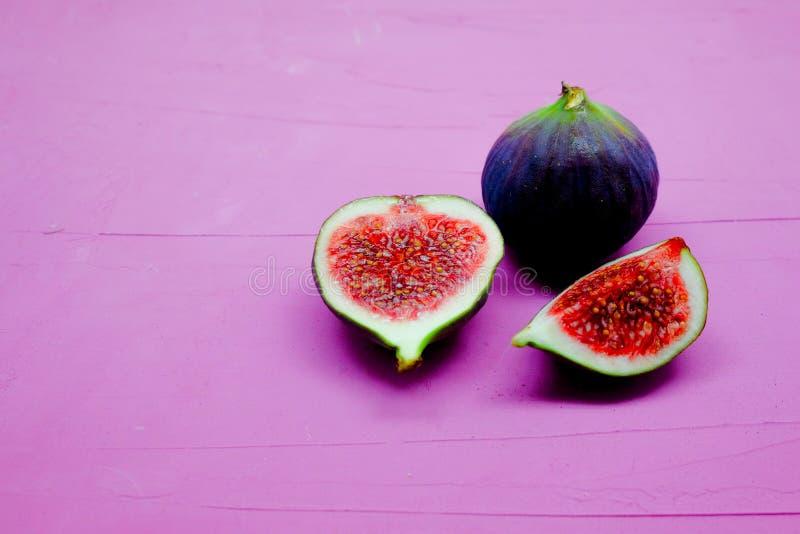 Fichi dolci maturi, frutta con la metà e quarto su fondo rosa immagini stock libere da diritti