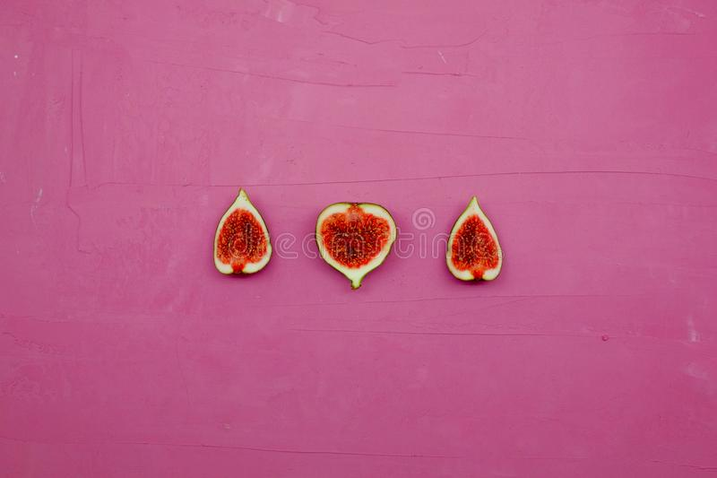 Fichi dolci maturi, frutta con la metà e quarto su fondo rosa fotografia stock libera da diritti