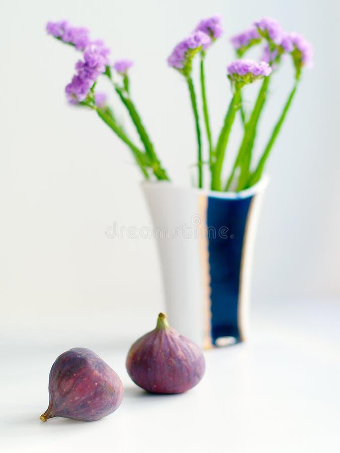 Fichi e vaso con i fiori fotografia stock libera da diritti
