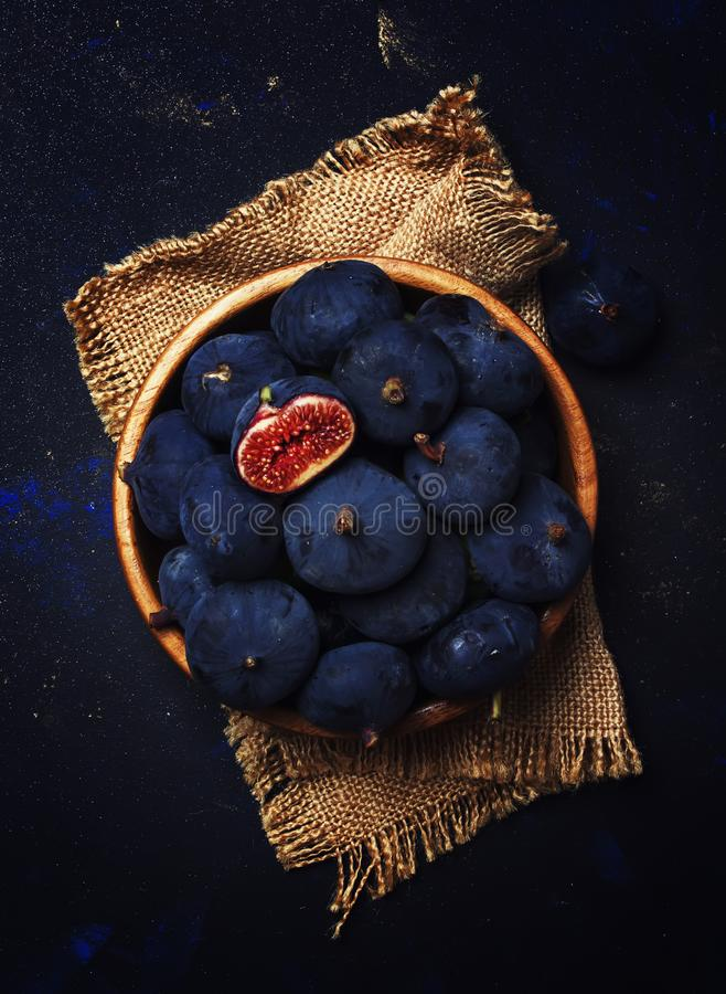 Fichi freschi blu maturi in una ciotola di legno, fondo scuro, vista superiore fotografia stock libera da diritti