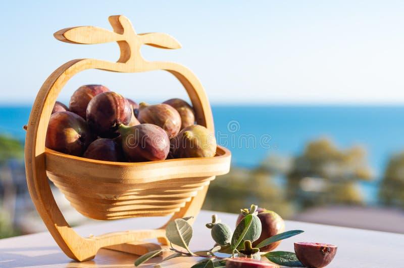 Fichi freschi Frutti del fico in un vaso di legno contro lo sfondo del mare Spazio libero del raccolto di estate per testo immagine stock libera da diritti