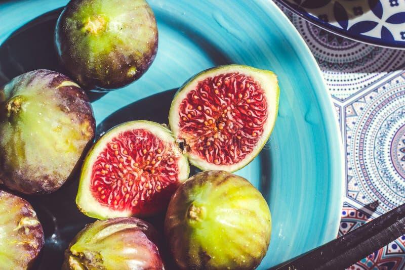 Fichi maturi taglio del mezzo e di tutto sul piatto blu; fondo della frutta fotografia stock