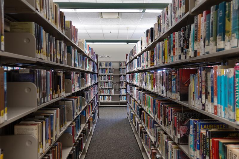 The fiction aisle of a public library showing rows of books stock images