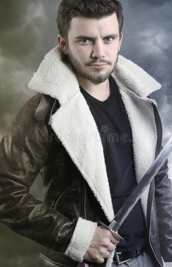 Fictional character - young man holding a saber. Young man holding a saber over a cloudy background stock photo