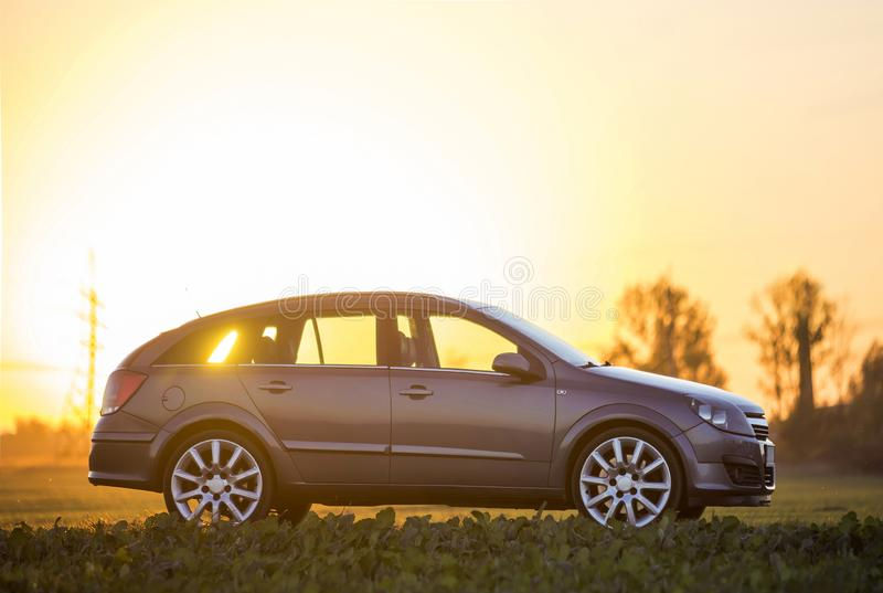 Fictional non existent modified image of a car. Gray car parked in countryside on blurred rural landscape and orange sky at sunset. Copy space background stock photography