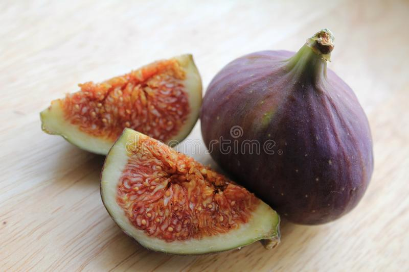 Figs on the wooden desk. Ficus carica is an Asian species of flowering plant in the mulberry family, known as the common fig. It is the source of the fruit also royalty free stock photos