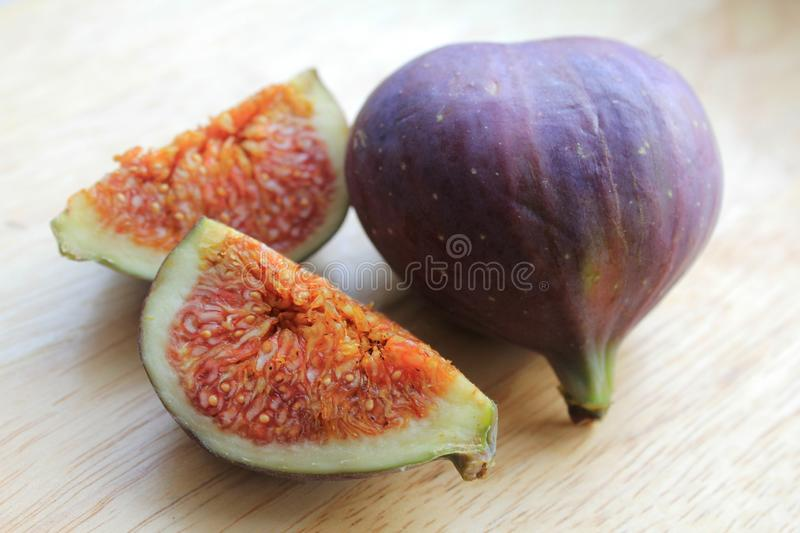 Figs on the wooden desk. Ficus carica is an Asian species of flowering plant in the mulberry family, known as the common fig. It is the source of the fruit also stock photography