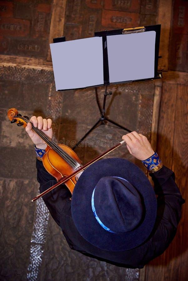 Fiddler in un cappello che gioca il violino fotografia stock