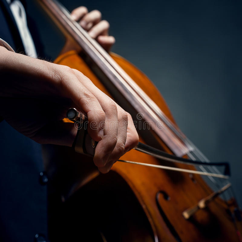 Fiddlestick in hand cellist. On a black background royalty free stock photos
