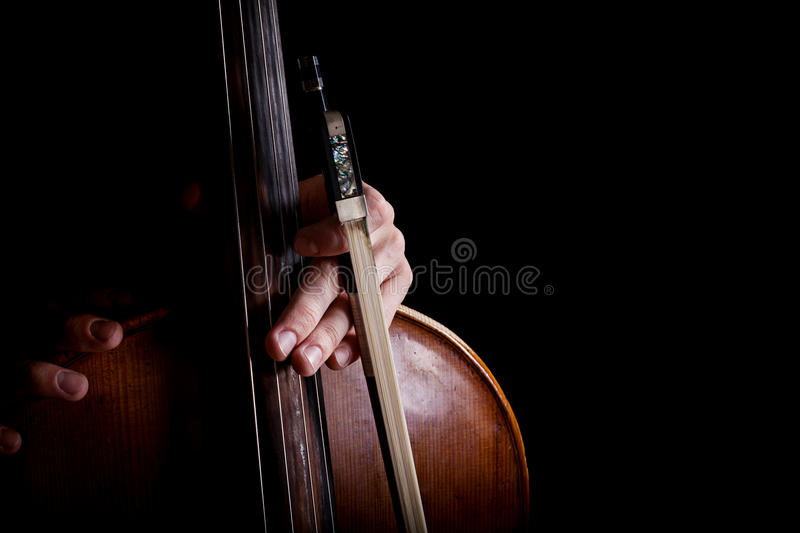 Fiddlestick in hand cellist. On a black background royalty free stock images