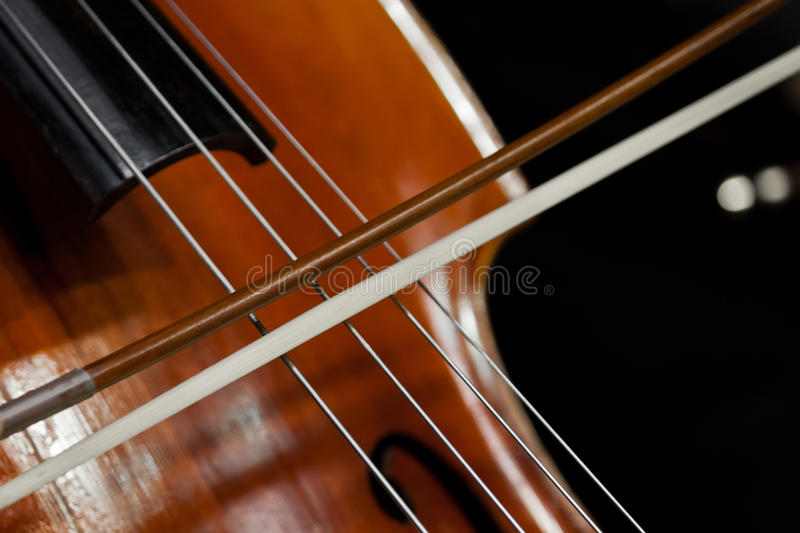 The fiddlestick on the strings of the cello. Closeup royalty free stock photo