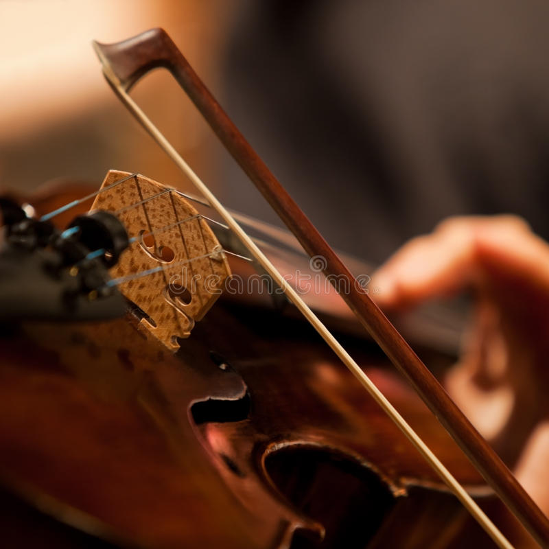 The fiddlestick on the strings violin. Closeup royalty free stock photos